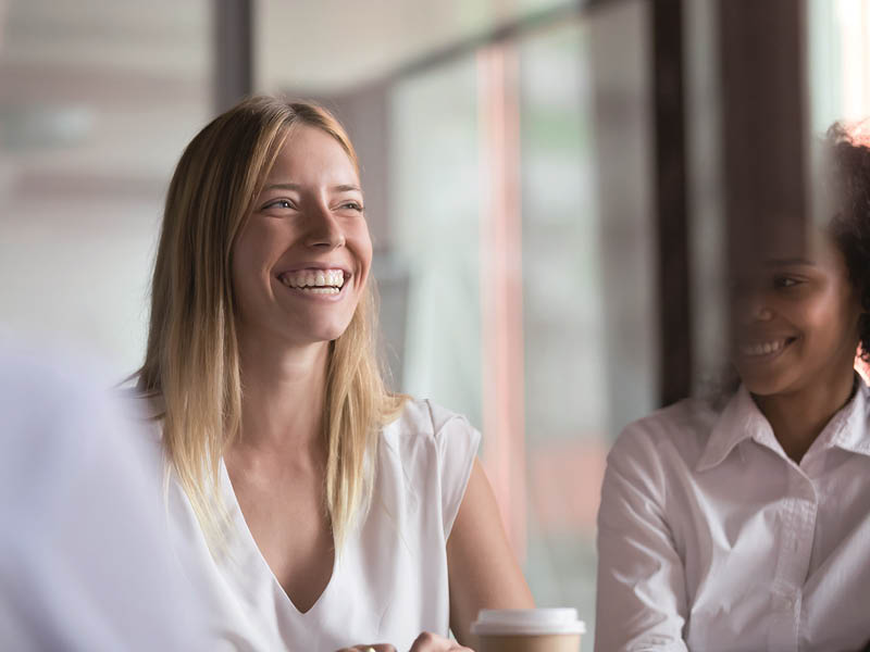 two ladies in office environment smiling